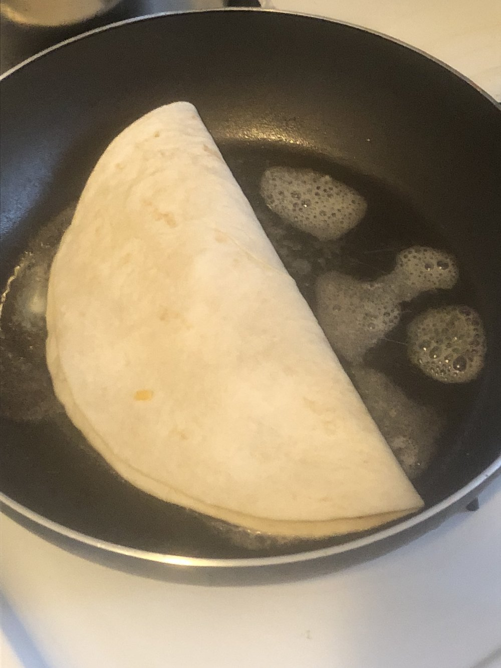 Put your butter in your medium skillet, and cook until the pan is hot. Fold the side of quesadilla over to cover the insides and place in the pan. Allow for the quesadilla to cook and for the cheese to melt, flipping the quesadilla on both side to allow for even cooking.