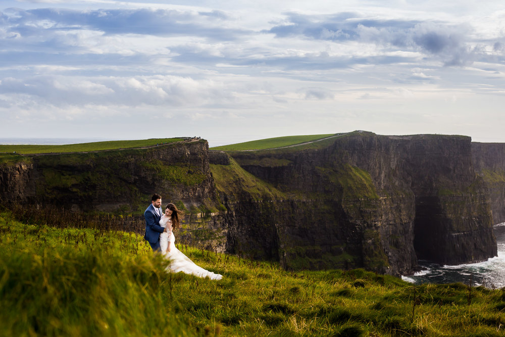 couple during their wedding portraits on the cliffs of moher by a south florida wedding photographer near the cave in harry potter and the half blood prince
