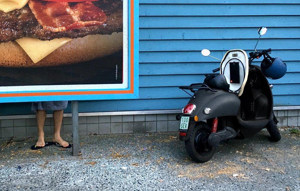 Mooi beeld van de unu scooter met een blauwe muur en hamburger poster op de achtergrond