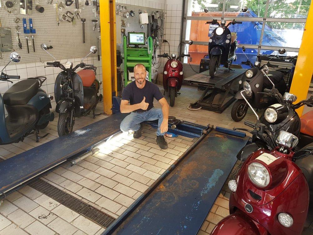 Ralf Thiele omringt door unu's, in de partnerwerkplaats Opel Häusler in München
