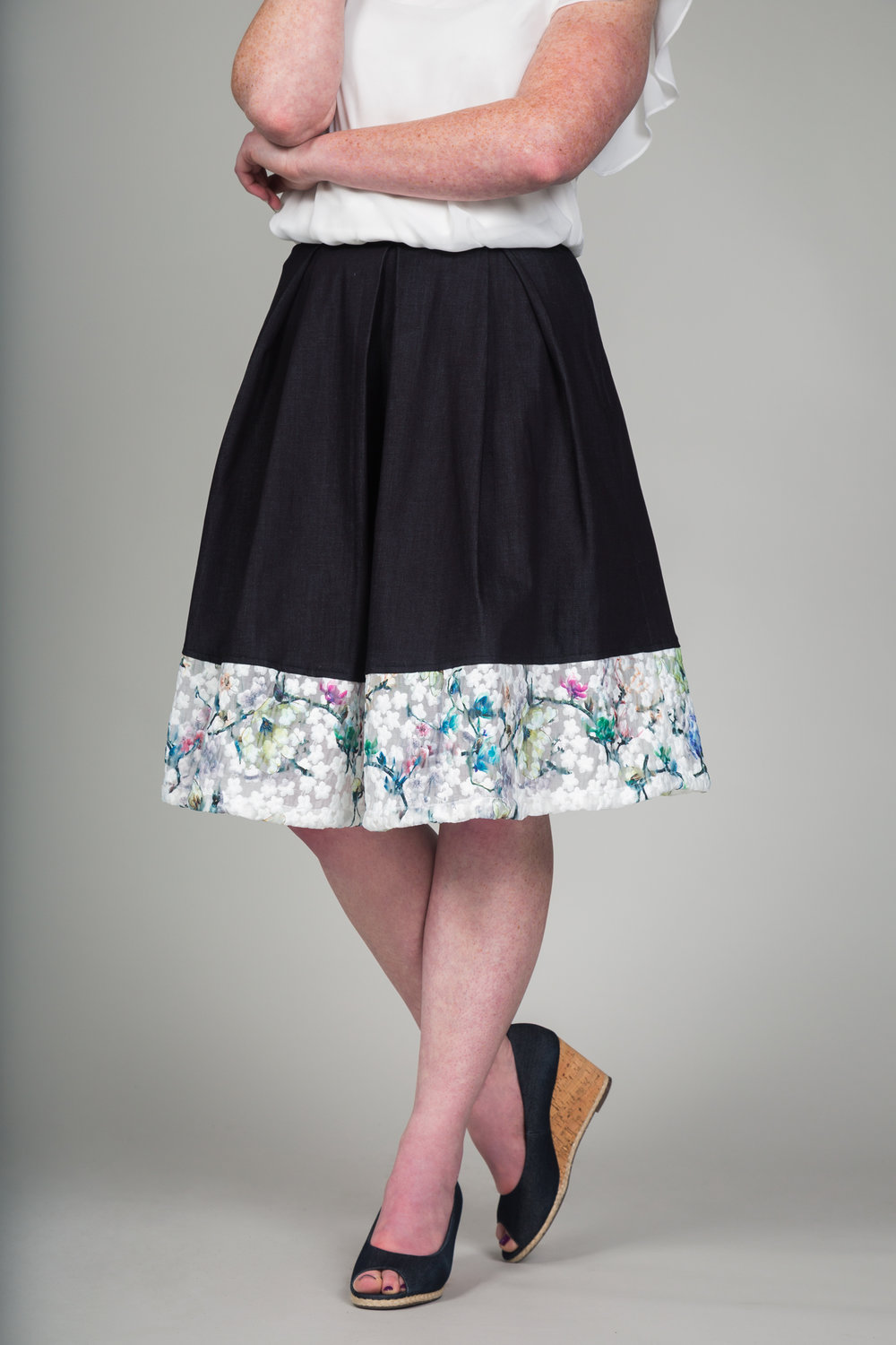 """This is my version of the professional denim skirt.  I incorporated the floral print as a border for the skirt to give it some color.  The box pleats both front and back gives the skirt structure and adds the the professional look.  By using a dark washed denim this skirt can worn to work or any other social event.  Overall, I wanted to create a cohesive collection and have pieces that you can pair with each other."" - BhavyJ"