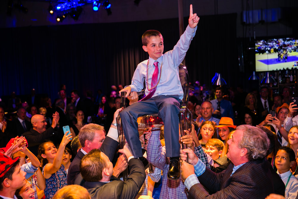 A happy client gets carried by the crowd at his Bar Mitzvah