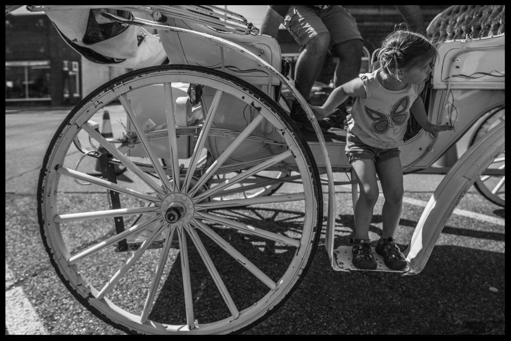Little girl climbing down from a carriage, black and white