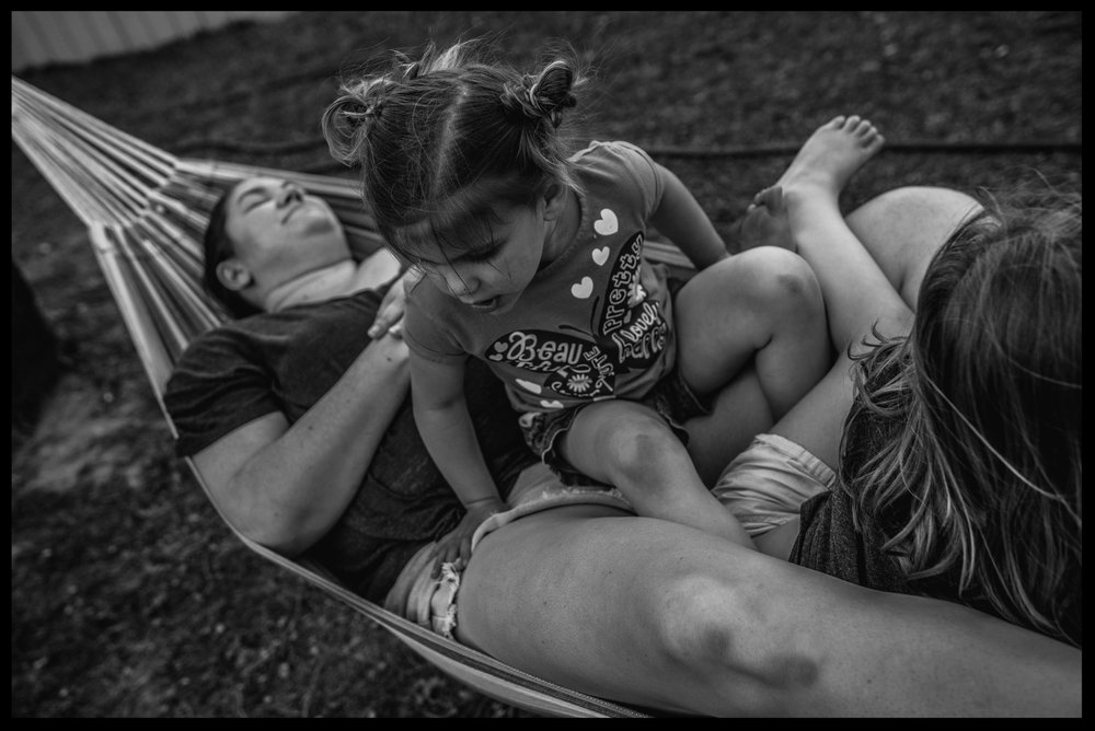 Two sisters sitting on their mother in a hammock, black and white