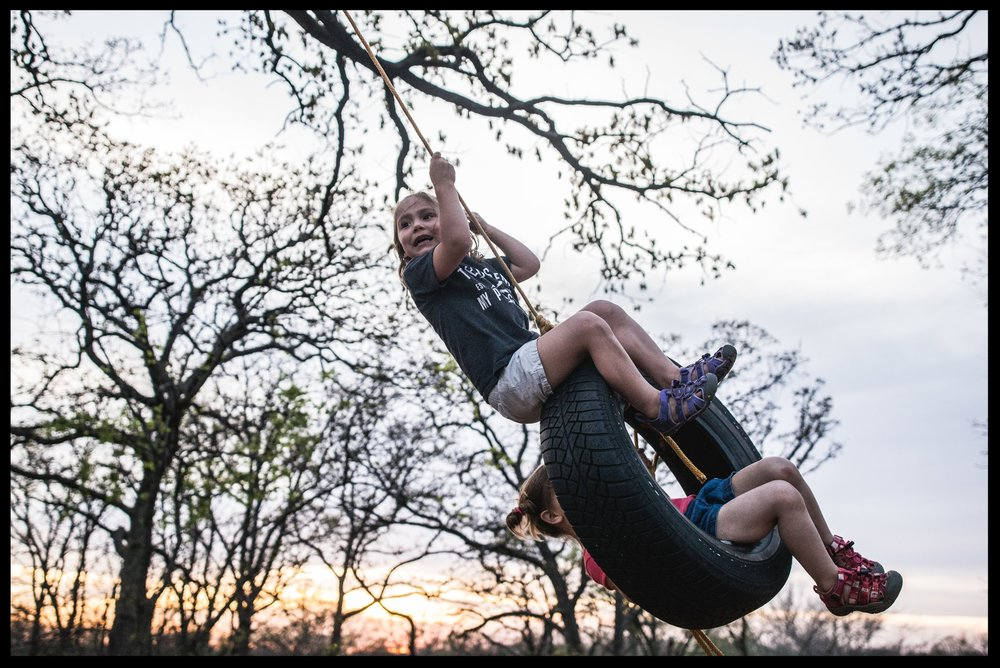 Sisters swinging on a tire swing with a colorful sunset as a backdrop