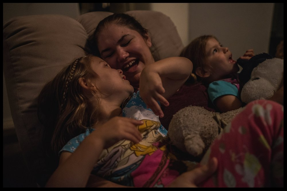 Mommy singing with her two daughters in the recliner before bedtime, color