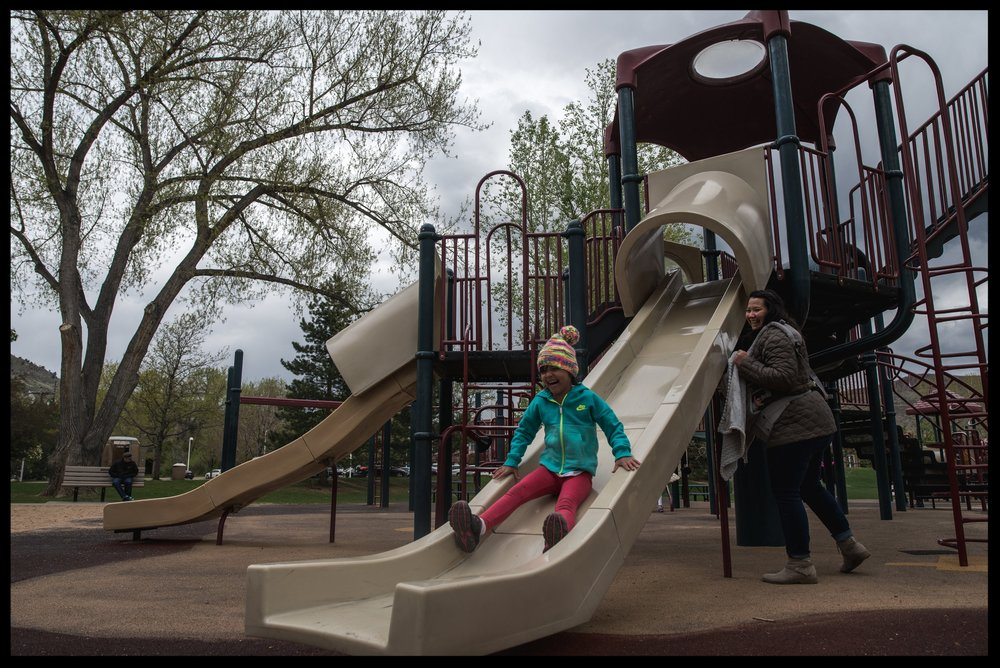 Mother watching her daughter slide down a slide at the park, color, Golden Colorado
