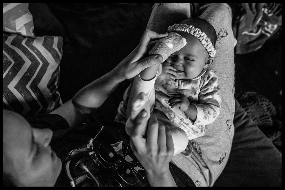Mom plays with baby's feet as baby smiles, black and white, Aurora, Colorado