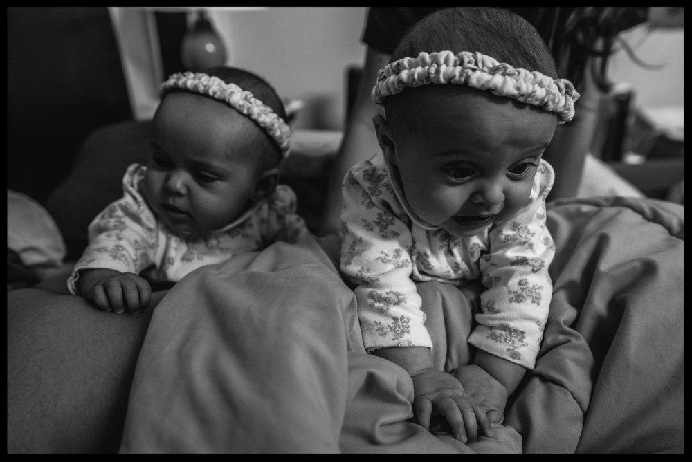 Twin girls pile on daddy in bed, black and white, Aurora, Colorado