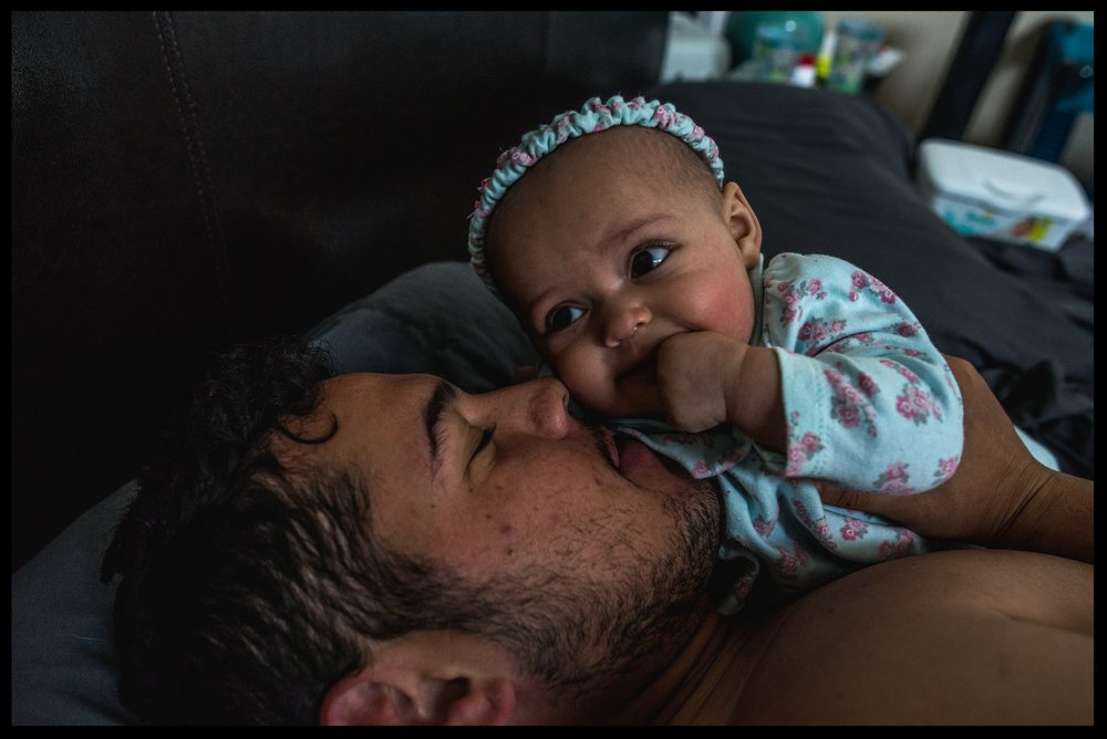 Daddy laying in bed kissing his smiling baby daughter, color, Aurora, Colorado
