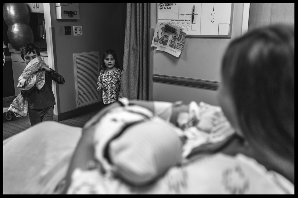 Brother and sister running into hospital room to meet their new baby sister, black and white, Stillwater, OK