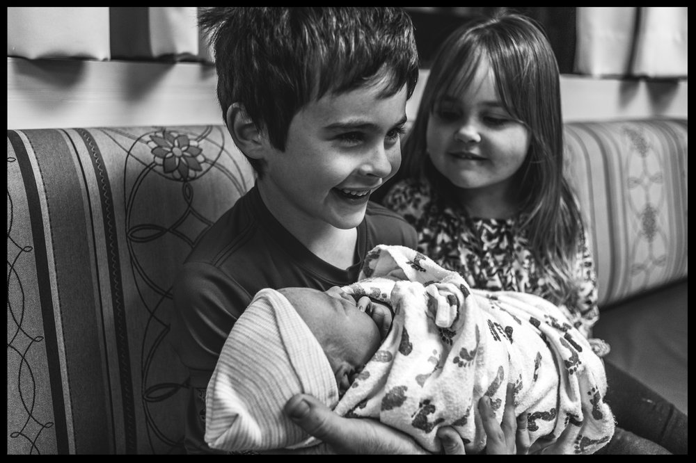 Little boy holding his new baby sister while his other sister looks on, black and white, Stillwater, OK