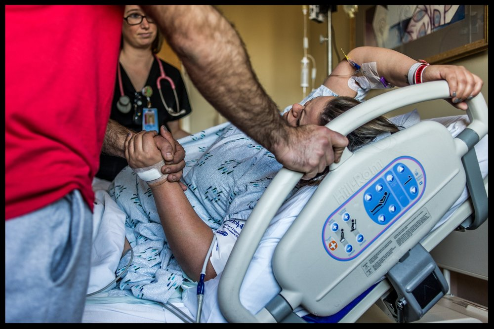 Woman in labor in a lot of pain while her husband holds her hand while a nurse watches on, color, Stillwater, OK