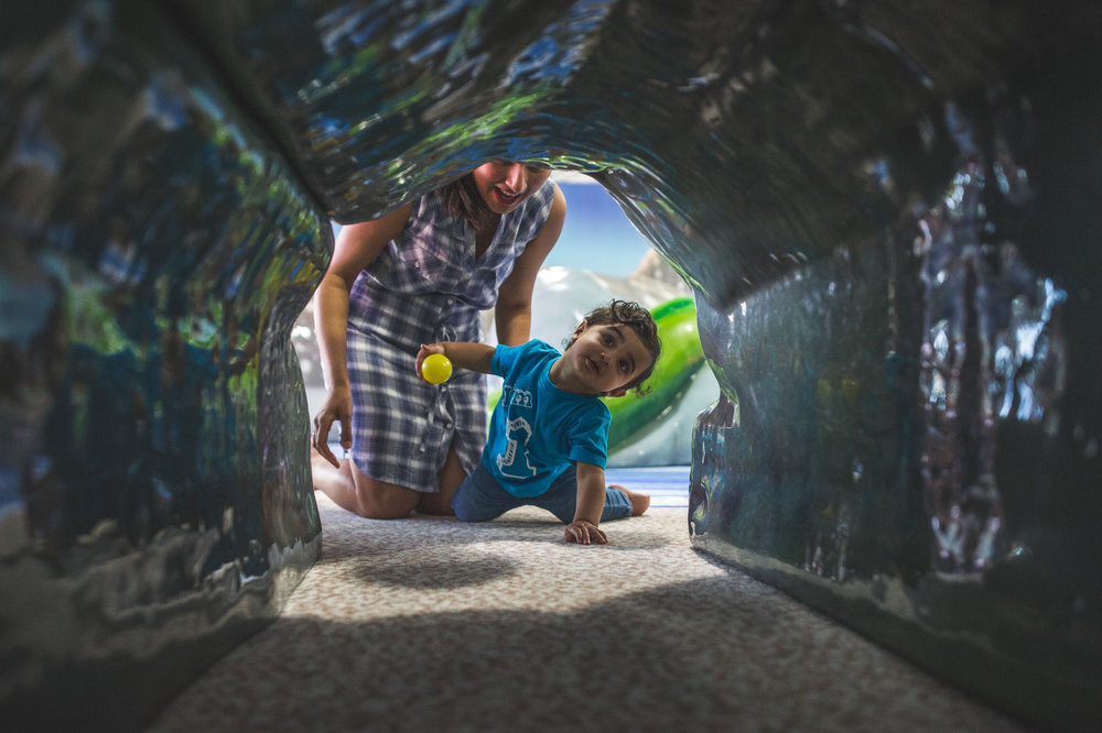 One year old crawls through a tunnel at the birthday party room at the Denver Aquarium while his mother encourages him