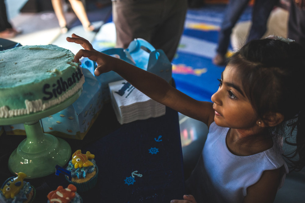 Little girl steals icing off of a cake at a birthday party at the Denver Aquarium