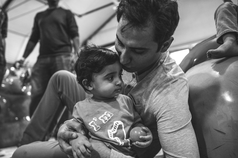 Father kisses his baby boy on his first birthday, black and white