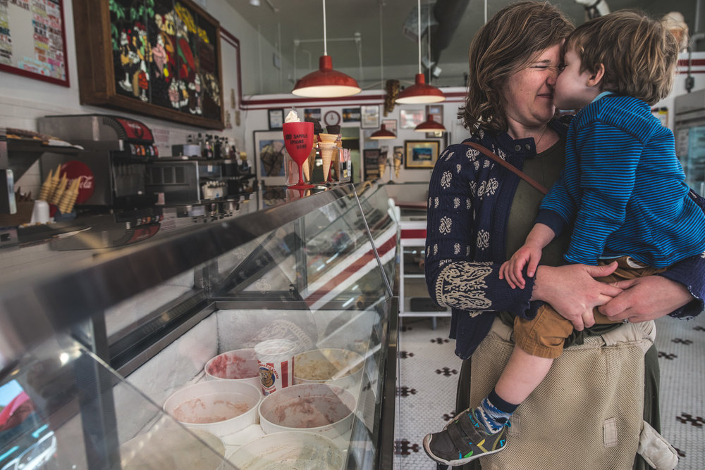 Mother and son smooshing their noses together as they wait to be helped at the ice cream shop, Denver, Colorado, color