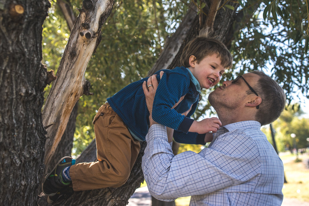 Father helping his son out of the tree as he goes in to give him a big kiss, Washington Park, Denver, Colorado, color