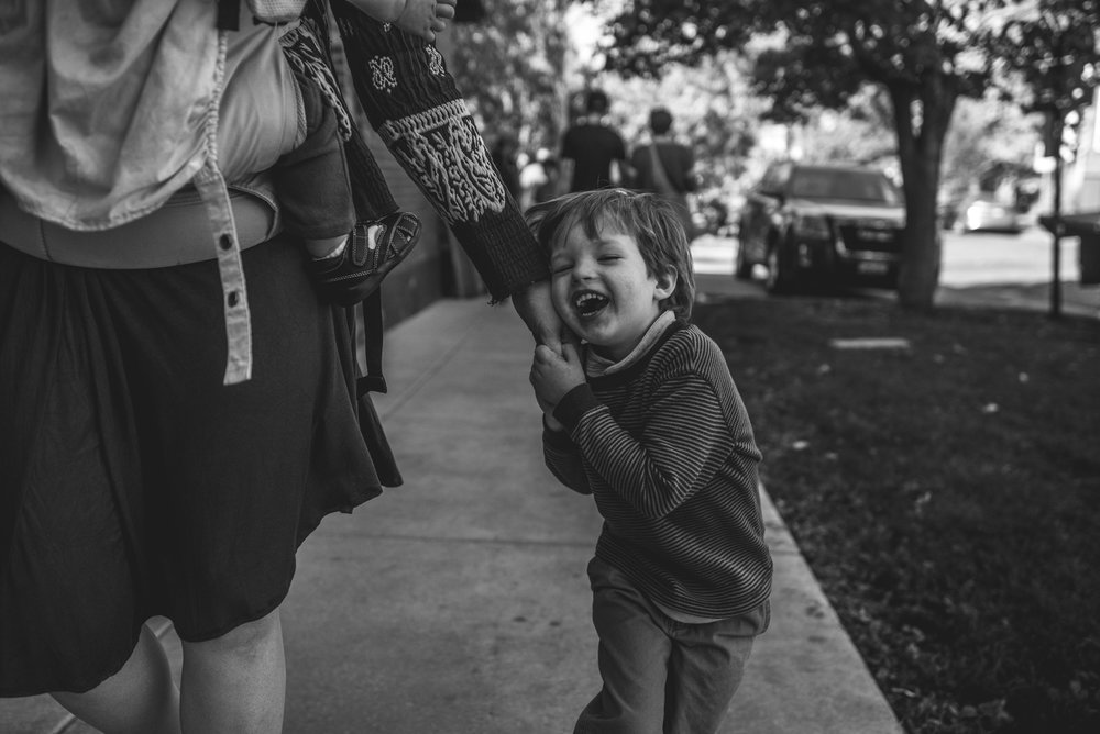 Little boy holding on to his mother's hand and smiling with joy, Pearl Street Farmer's Market, Denver, Colorado, black and white