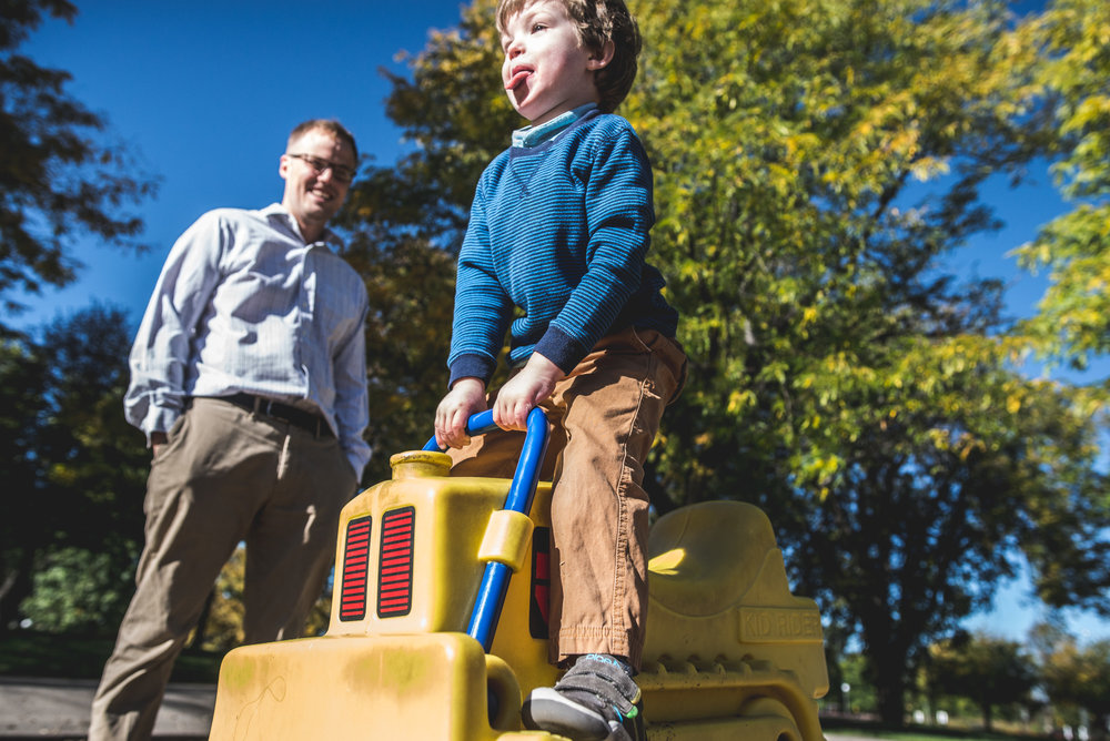 Little boy sitting on a bouncy toy in Washington Park, sticking his tongue out as dad smiles on, Denver, Colorado, color