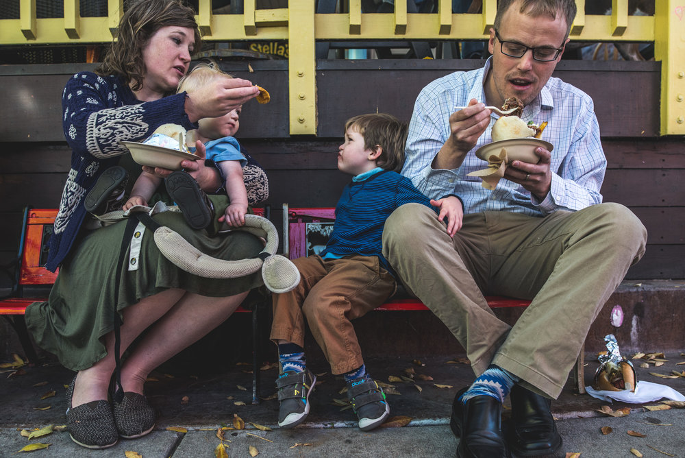 Family is sitting on a bench while mother tries to feed her son who doesn't want to eat what she's giving him, Pearl Street Farmer's Market, Denver, CO
