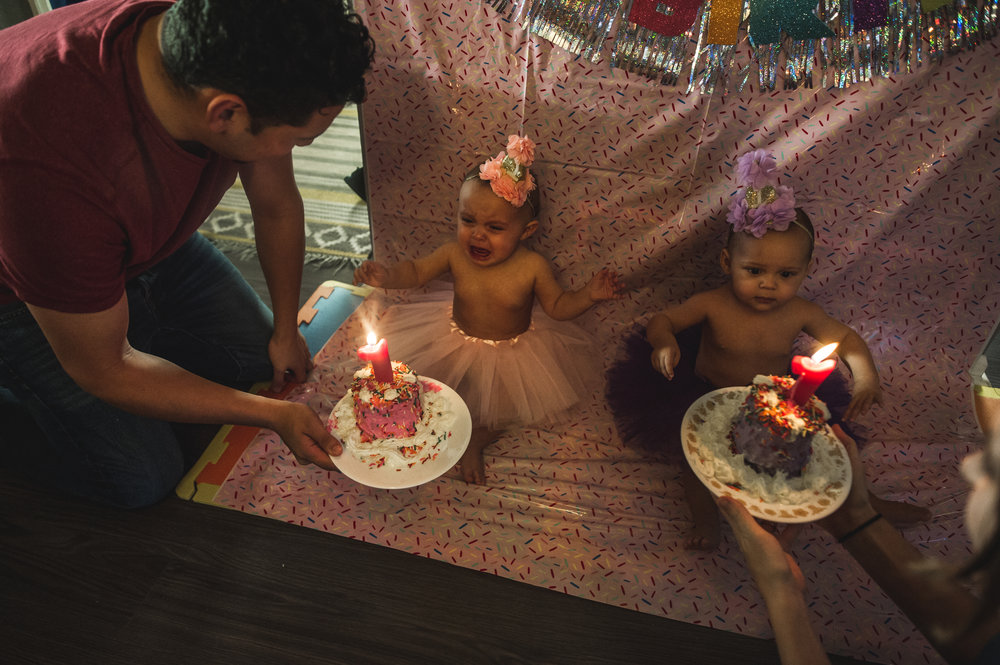 Parents bring out two birthday cakes for their one year old twins. One girl wears a purple tutu and party hat while her twin sister, who is crying, wears a pink tutu and party hat. Aurora, Colorado