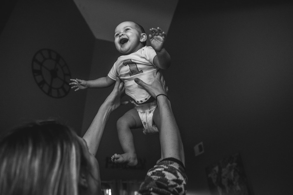 One year old girl smiles as her mother tosses her in the air, black and white, Aurora, Colorado