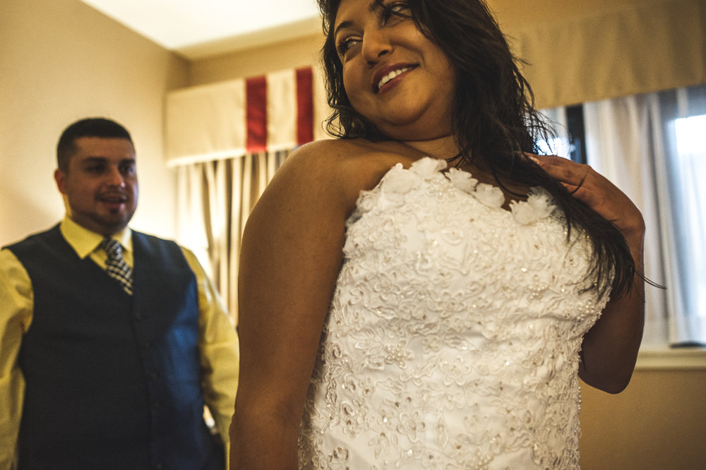 Groom looks at the back of his bride, whose dress he has just successfully tied for her, Estes Park, Colorado, color