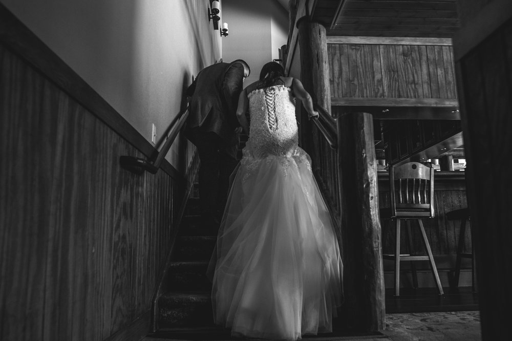Bride and groom walk up the stairs as the bride's dress flows down the steps, Estes Park, CO, black and white