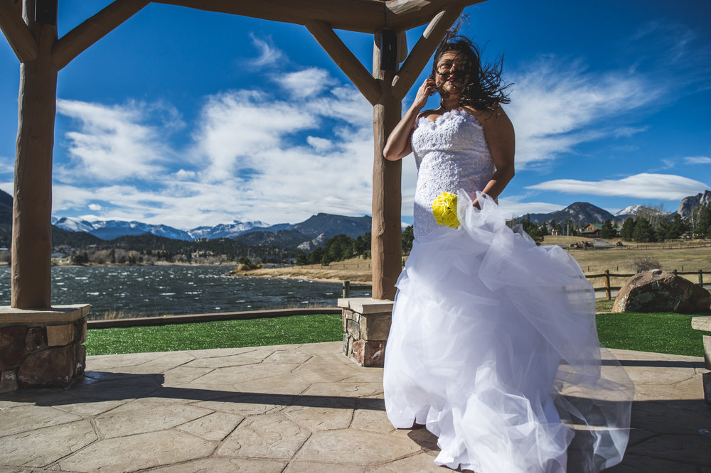 Bride stands in a gazebo at a resort in Estes Park, her hair and dress blowing wildly in the wind, color