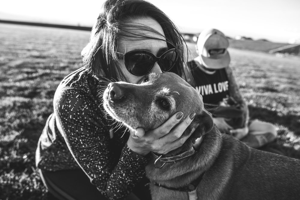 Woman holds her dogs face and kisses her on the cheek, black and white, Stapleton, Colorado