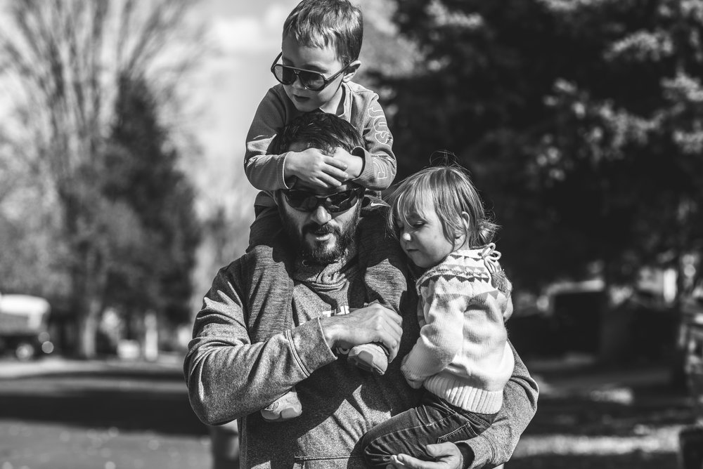 Father carrying his son on his shoulders and his daughter in his arms, black and white, Denver, Colorado
