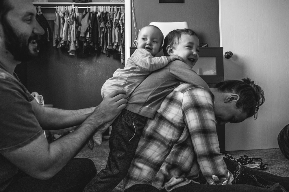 A woman bows her head as her 3 year old son hangs off of her back and her husband places their infant daughter on the back of their son, black and white, Denver, Colorado