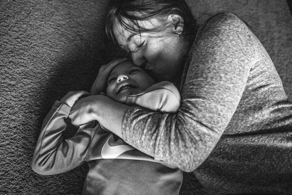Mother and her son cuddle on the floor as the mother kisses her son and he grins wide, black and white, Denver, Colorado