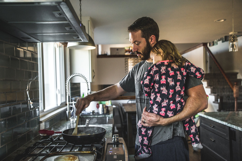 A father holds his young daughter while cooking breakfast, color, documentary photography session, Denver, Colorado