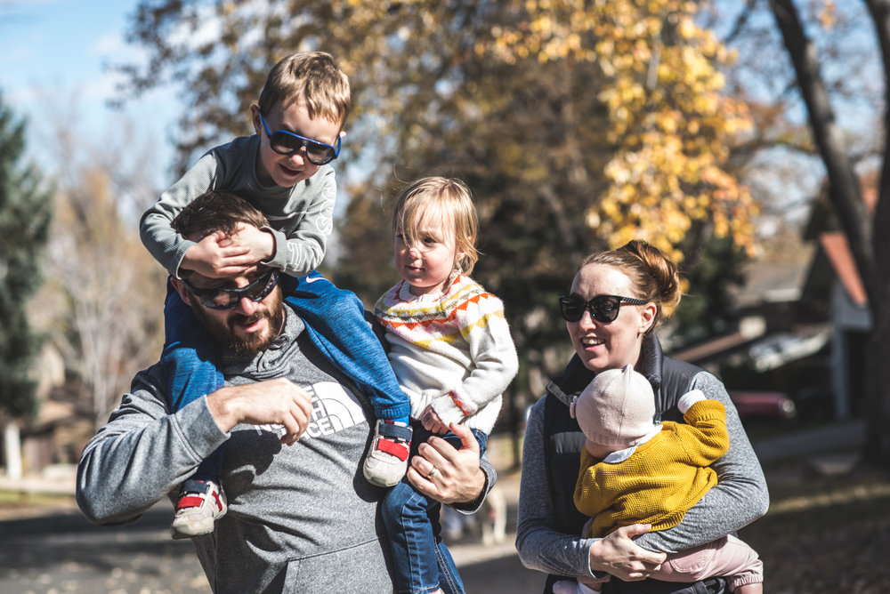 A father has his son on his shoulders and holds his daughter in his other hand while his wife walks beside him holding their 3rd child during a day in the life photography session in Denver, Colorado