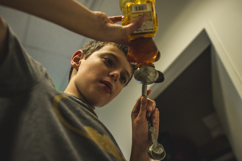 Underneath shot of a boy in a batman shirt pouring honey into a measuring spoon during a cooking class in Littleton, Colorado, color