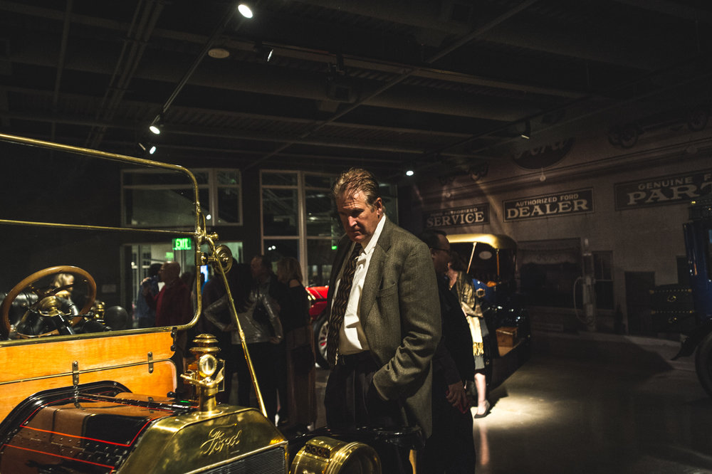 A man in a suit looks at a vintage Ford in the Vehicle Vault in Parker, Colorado, photo in color
