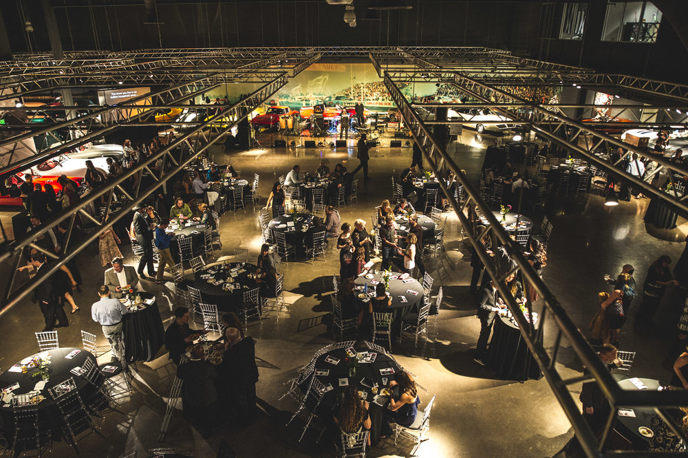 An overhead view of the Vehicle Vault main floor in Parker, Colorado. In the frame you can see the industrial supports overhead and tables filled with guests attending the Autism Society Winter Fundraiser. The walls are lined with vintage cars. Photo in color.
