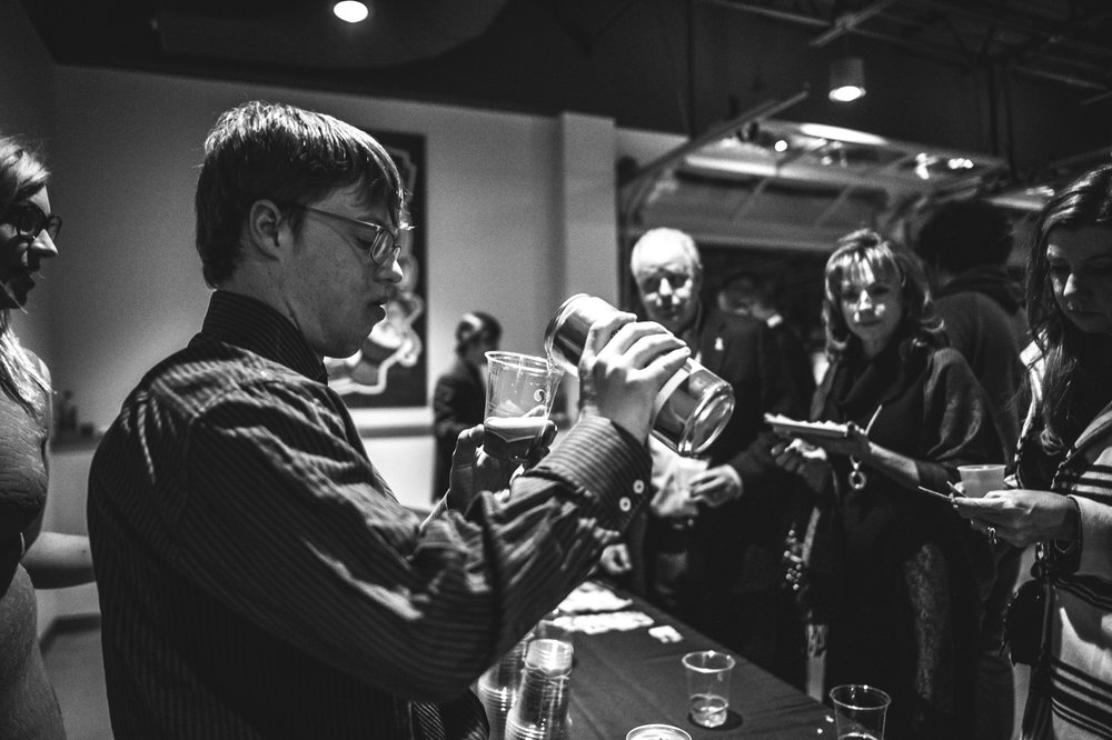 An employee of Brewability Lab pours a beer for guests at the Autism Society's Winter Fundraiser at the Vehicle Vault in Parker, CO. Photo in black and white.