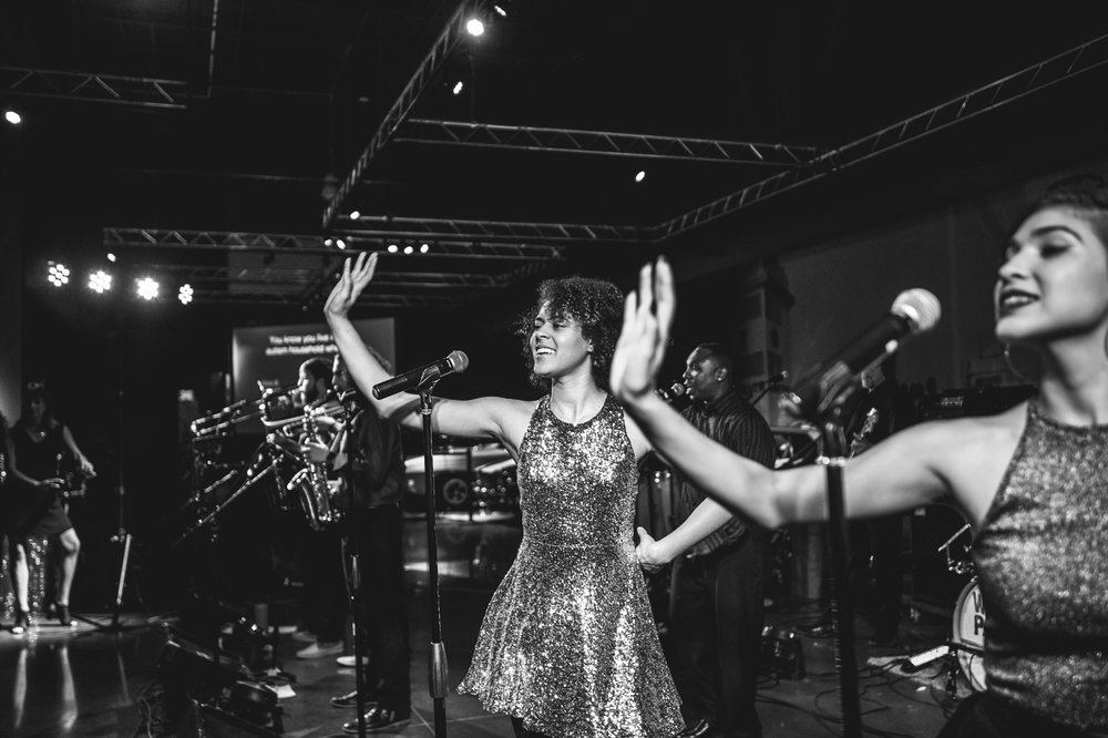 The vocalists of the Wash Park Band do a choreographed dance move during their performance at the Autism Society's Winter Fundraiser. Black and white.
