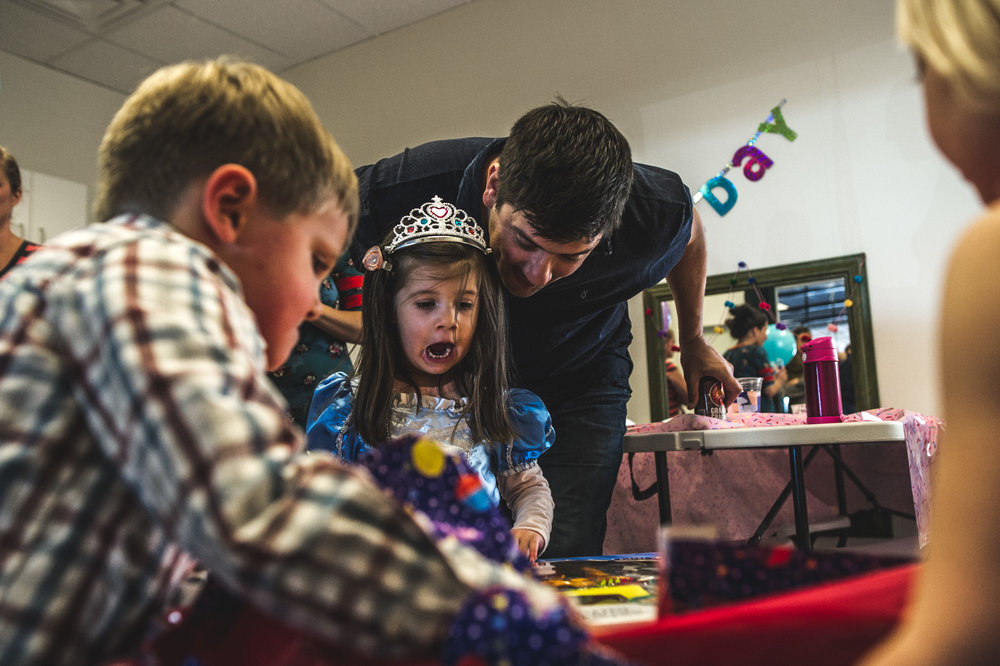 A little girl's mouth gapes in excitement as she opens presents on her birthday. The girl is wearing a princess dress and crown and her dad hovers above her, smiling at her joy. Photo is in color.