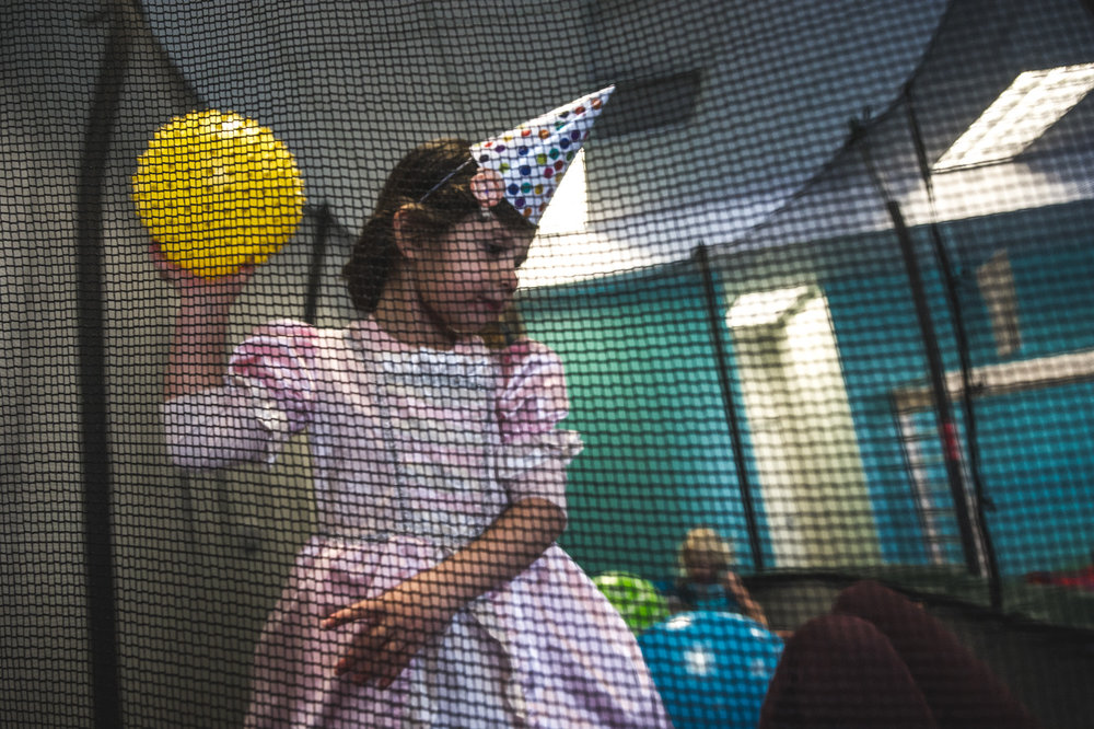 Little girl in a party hat and princess outfit aims a yellow ball at her friend on a trampoline at Family Connections Thera-play gym in Littleton, Colorado.