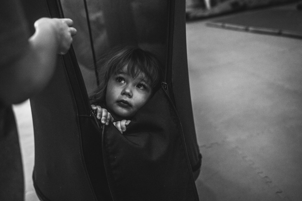 A little girl peeks out from her hiding spot in a giant swing pod during a documentary event photo session in the Family Connections Thera-play kids' gym in Litteton, Colorado. Photo in black and white.