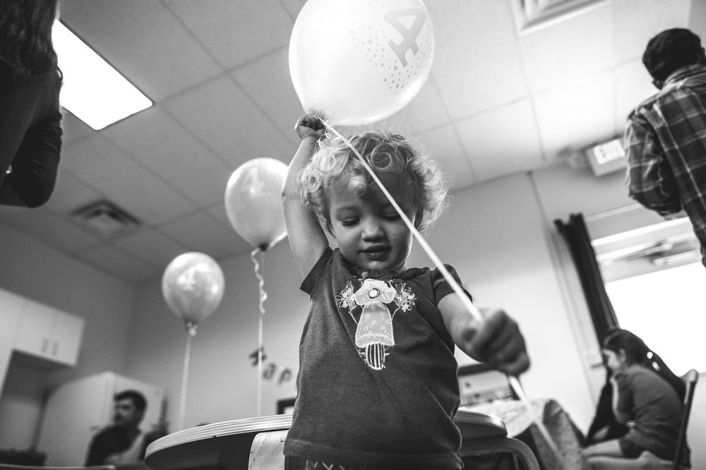 Black and white photo of a young girl playing with a balloon at a birthday party at Family Connections Thera-play kids' gym in Littleton, Colorado