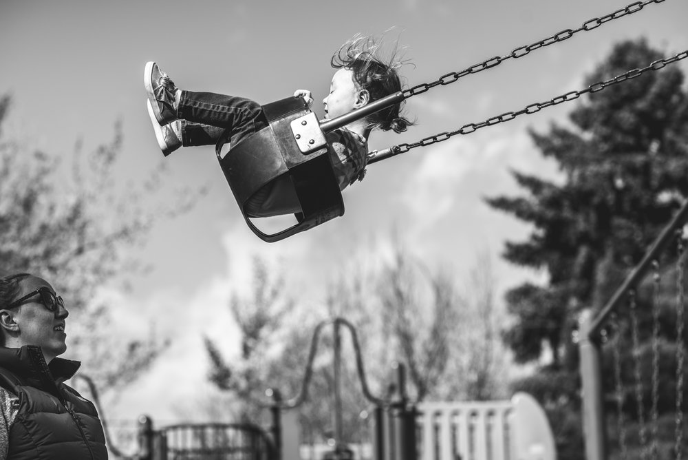 Black and white photo of a little girl swinging high in the sky as her mother watches from below in a park in Denver, Colorado