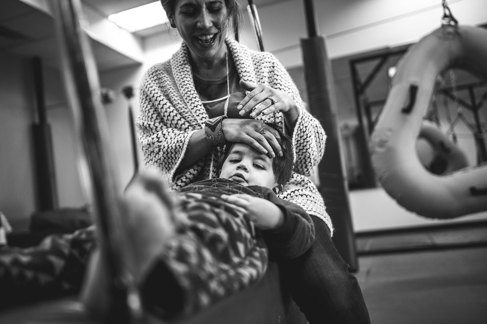 Black and white photo of a mother and son on a long swing at the Family Connections kids' gym in Littleton, Colorado. The young boy is stretched out on the swing, his head in his mother's lap as she strokes his hair.
