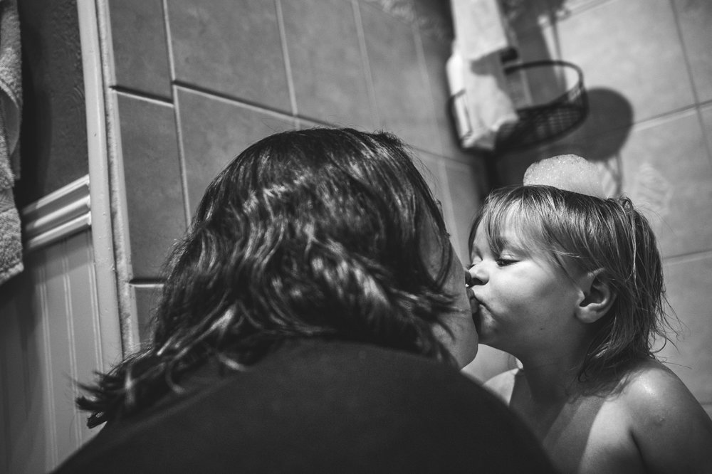 Black and white photo of a mother and daughter giving each other a kiss while the young girl is in the bathtub with a floof of bubbles on her head, Arvada, Colorado