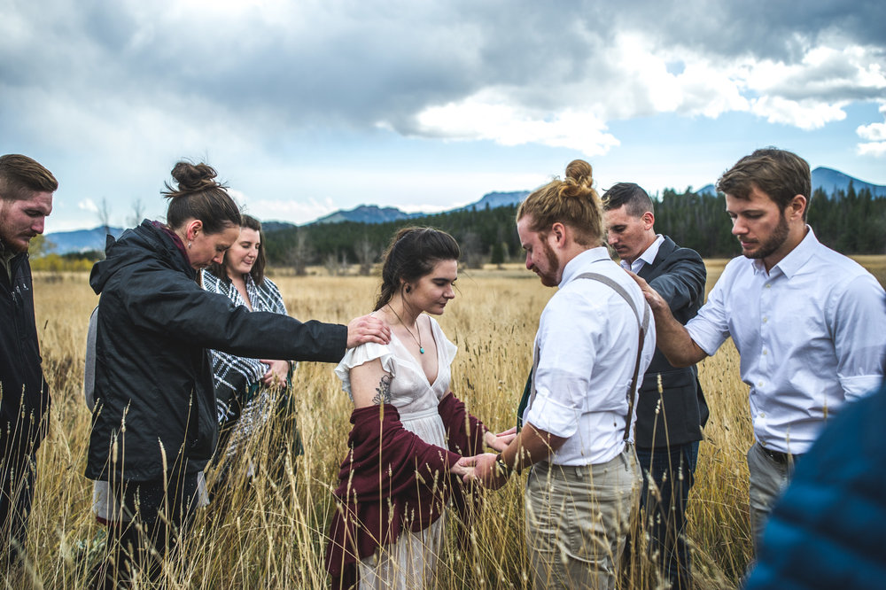 Color photo of family and friends praying over the bride and groom at an outdoor elopement in a field in a valley at Rocky Mountain National Park