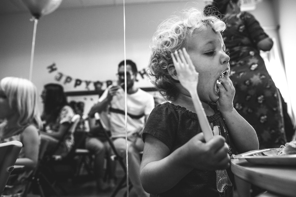 Black and white photo of a cute little curly-haired girl cramming birthday cake in her mouth with her hands at a birthday party thrown at Family Connections kids' gym in Littleton, CO